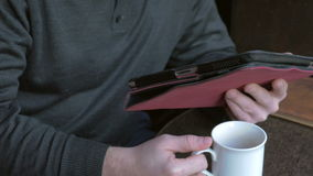 Businessman working on a tablet pc and drinking coffee in a coffeeshop stock video footage