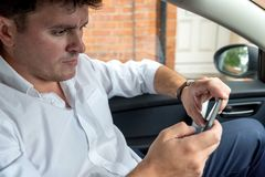 Businessman working on tablet and smartphone inside car on bright day royalty free stock image