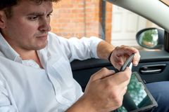 Businessman working on tablet and smartphone inside car on bright day royalty free stock photo