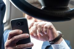 Businessman working on tablet and smartphone inside car on bright day royalty free stock images