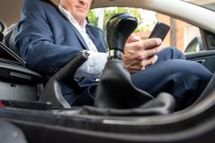 Businessman working on tablet and smartphone inside car on bright day stock image