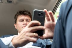 Businessman working on tablet and smartphone inside car on bright day stock photos