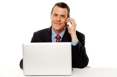 Businessman working and talking on cell phone Royalty Free Stock Images