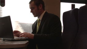 Businessman Working on a Train. Stock Video Footage of a Businessman using his laptop on a Train stock footage