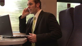 Businessman Working on a Train. Stock Video Footage of a Businessman using his laptop on a Train stock video footage