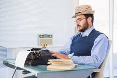 Businessman working on typewriter while smoking Stock Images