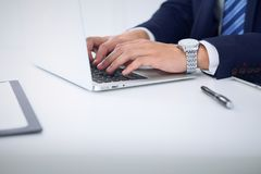 Businessman working by typing on laptop computer. Man`s hands on notebook or business person at workplace. Employment  o Royalty Free Stock Images