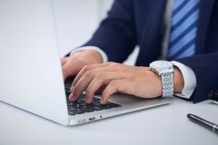 Businessman working by typing on laptop computer. Man`s hands on notebook or business person at workplace. Employment  o Stock Image