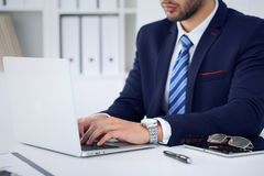 Businessman working by typing on laptop computer. Man`s hands on notebook or business person at workplace. Employment  o Royalty Free Stock Photos