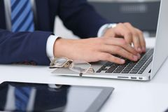 Businessman working by typing on laptop computer. Man`s hands on notebook or business person at workplace. Employment  o Stock Photos