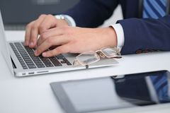 Businessman working by typing on laptop computer. Man`s hands on notebook or business person at workplace. Employment  o Stock Photo