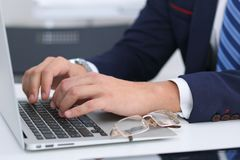 Businessman working by typing on laptop computer. Man`s hands on notebook or business person at workplace. Employment  o. R start-up concept Stock Photos