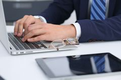 Businessman working by typing on laptop computer. Man`s hands on notebook or business person at workplace. Employment  o Royalty Free Stock Photography