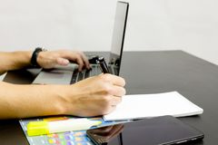 A man prints on a laptop, lying next to the phone, tablet glasse royalty free stock images