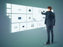 Businessman working with virtual surface. Young business man touching on futuristic virtual screen Stock Photo