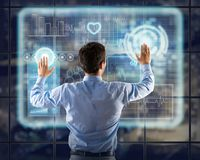 Businessman working with virtual technologies. Businessman working with modern virtual technologies, stands back, hands touching the screen Stock Images