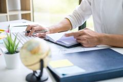 Businessman working writing making note business plan and graphic designer with computer in office.  stock photography