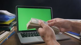 Businessman at workplace counting many American 100 bills with laptop with a green screen on the desk. Concept of salary
