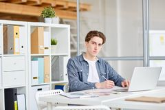 Businessman at workplace. Portrait of young casual businessman working on laptop at his workplace Royalty Free Stock Photos