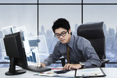 Businessman works with computer and calculator. Young businessman working with calculator and virtual financial graph on the computer monitor, shot in the office Stock Images