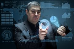 The businessman works with a futuristic virtual interface. Working with a virtual screen and managing business processes. Future technologies Stock Photos