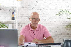 A businessman works in his office. A businessman with a pink polo shirt works in his office Royalty Free Stock Image