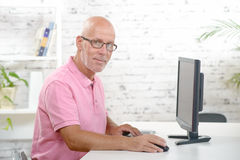 A businessman works in his office. A businessman with a pink polo shirt works in his office Royalty Free Stock Photo