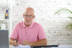 A businessman works in his office. A businessman with a pink polo shirt works in his office Stock Photos