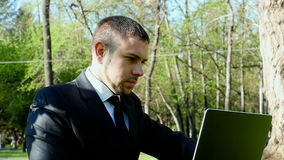 Businessman works with laptop in the city park stock footage