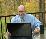 Businessman Works with Laptop at Home. Businessman works at home outdoors with his laptop Royalty Free Stock Images