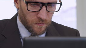 Businessman works on laptop. Middle aged businessman working on laptop at the office. Close up of caucasian bearded man in glasses looking at the screen stock video footage