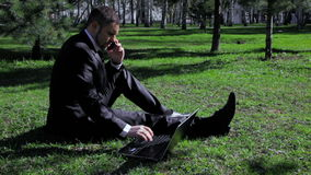 Businessman works with laptop and mobile phone in the city park
