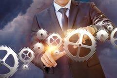 Businessman works with a mechanism . Businessman works with a mechanism on sky background Stock Image