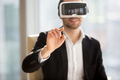 Businessman works in office augmented reality. Entrepreneur in VR headset interacts with application virtual interface, pressing invisible buttons or selects stock photos