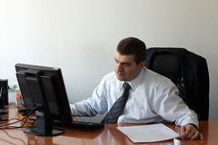 Businessman works in office. The businessman works in the office by computer Royalty Free Stock Image