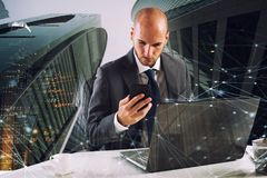 Businessman works with smartphone and laptop. In a modern office Stock Photos
