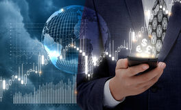 Businessman works at the stock exchange via a mobile device. Stock Photo
