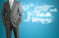 Businessman with world map, clouds, and graphs Royalty Free Stock Photos