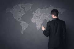 Businessman with world map. Young businessman in black suit standing in front of a black world map Royalty Free Stock Image