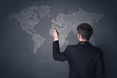 Businessman with world map. Young businessman in black suit standing in front of a black world map Royalty Free Stock Photo
