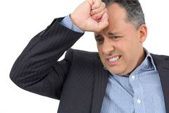 Businessman worried about company. He is wearing social clothing. Businessman is with his hand on his face and very worried. Do not know what to do. He wears Royalty Free Stock Images