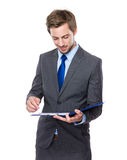 Businessman write on clipboard Royalty Free Stock Images