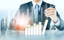 Businessman write increasing graph with city background. Business growth Royalty Free Stock Photo