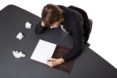 Businessman - writers block. Isolated studio shot of a businessman suffering from writers block trying again after several failed starts Royalty Free Stock Photos