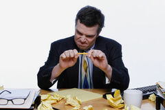 Businessman with Writers' Block. Man in a business suit sitting at his desk frustrated and trying to snap a pencil. Surrounded by crumpled up pieces of paper Royalty Free Stock Images