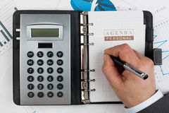Businessman writes in a diary. Diary, calculator,hand and pen  on a background of diagrams and graphs Stock Image