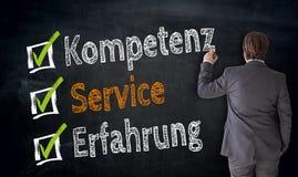 Businessman writes Kompetenz, Service, Erfahrung & x28;in german comp stock photography