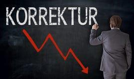 Businessman writes Korrektur in german correction on blackboar Stock Photos