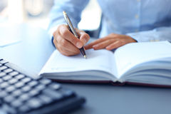 Businessman writes in a notebook. While sitting at a desk Royalty Free Stock Photography