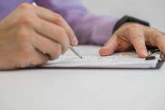 Businessman writes in a notebook while sitting at a desk. Royalty Free Stock Image
